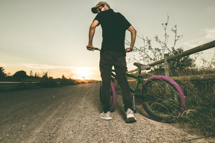 Rear View Of Man With Bicycle On Road During Sunset