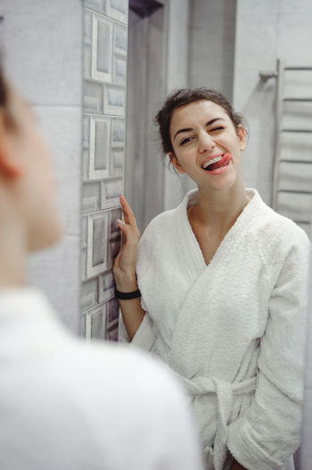 Young woman in bathrobe standing at bathroom