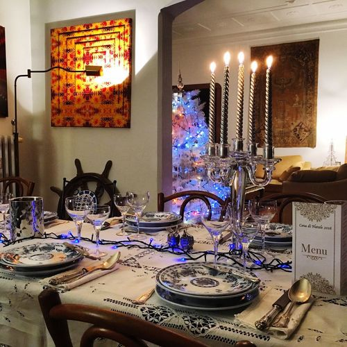 Christmas dinner at home Indoors  Illuminated No People Lighting Equipment Table Household Equipment Domestic Room Home Home Interior Window Plate Arrangement Candle Night Absence Architecture Glowing Wall - Building Feature Large Group Of Objects Electric Lamp
