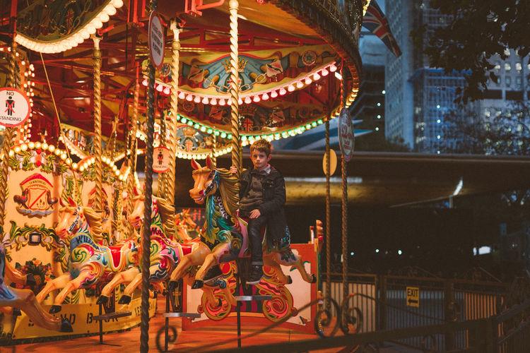 Boy sitting on illuminated carousel in amusement park