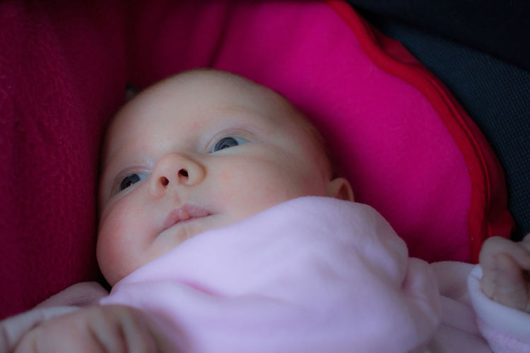 Close-up of cute baby girl looking away at home
