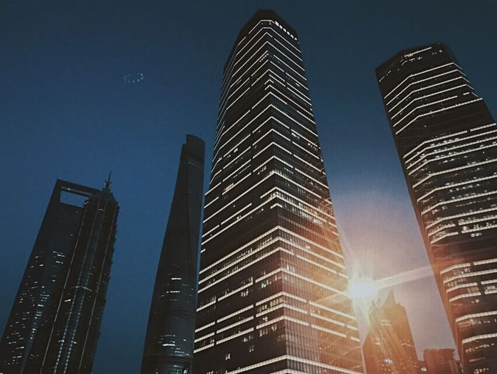 Low angle view of skyscrapers against sky at night