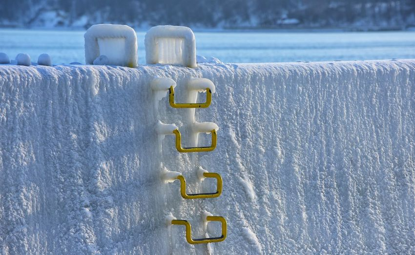 Close-up of metallic handles on snow covered wall