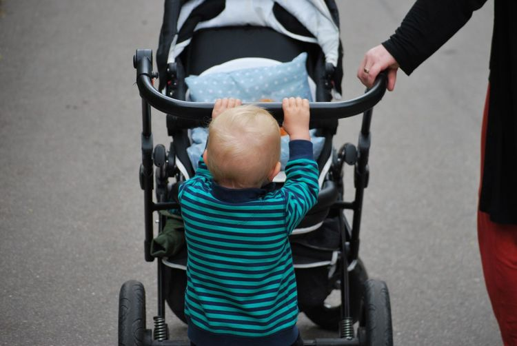 Cropped Image Of Person Walking With Boy Pushing Baby Stroller On Footpath