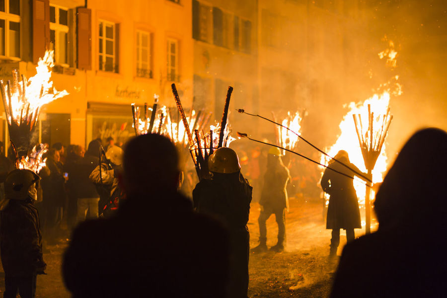 Chienbaese festival. Switzerland, Liestal, Rathausstrasse 25, 18th of February 2018. Festival participants carrying burning broom shaped wooden logs on their shoulders through the old town. Some people in the crowd are grilling sausages on the open fire. Flame Grilling Sausages Tradition Arts Culture And Entertainment Burning Celebration Chienbäse Crowd Culture Festival Fire Fire - Natural Phenomenon Flame Group Of People Heat - Temperature Large Group Of People Liestal Night Outdoors Real People Sparks Swiss Switzerland Wood - Material