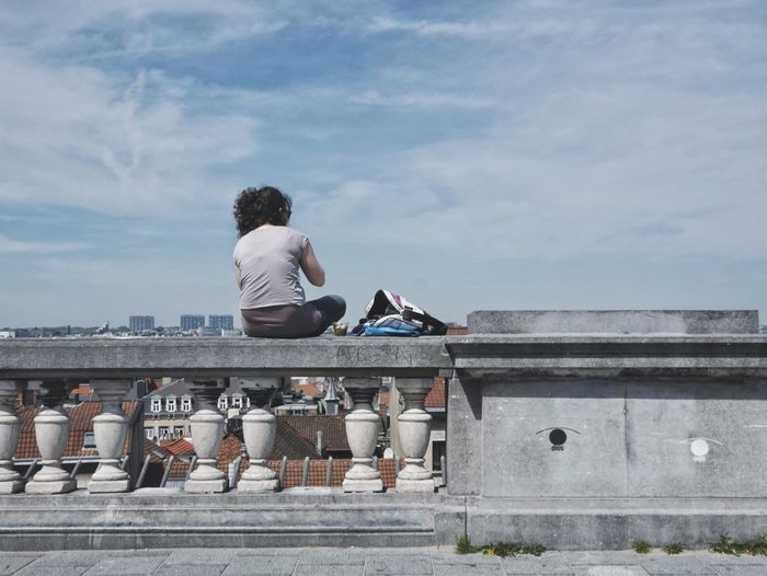 Rear View Of Woman Sitting In Railing Against Sky At City