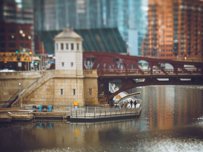 A couple walking their dog under a drawbridge on the chicago riverwalk