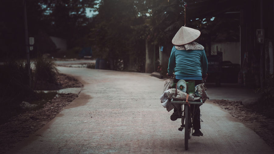 Rear view of woman with bicycle on road