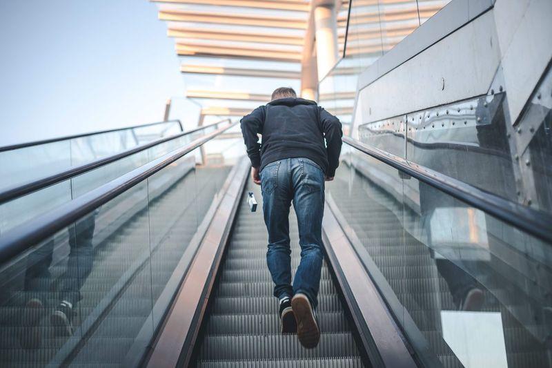 Rear view full length of man on escalator
