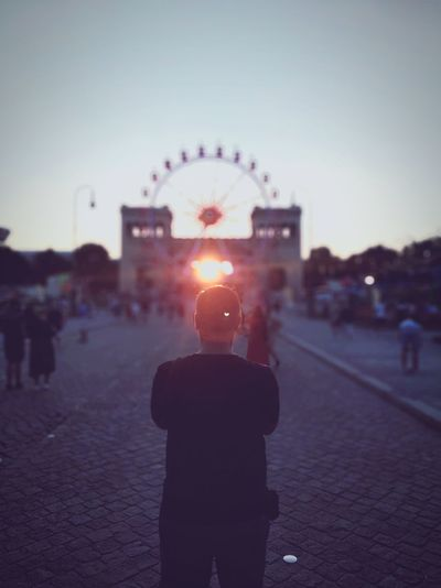 Rear view of man standing in amusement park against sky during sunset
