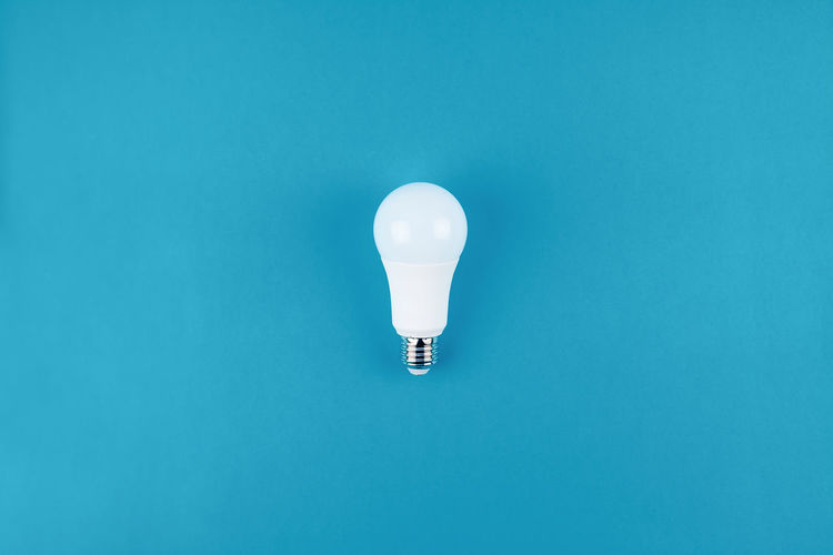 Low angle view of light bulb against blue background