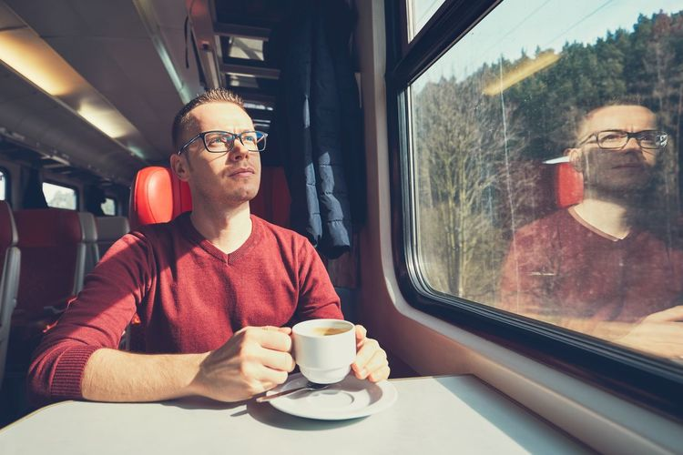 Young Man With Coffee Cup Traveling In Train