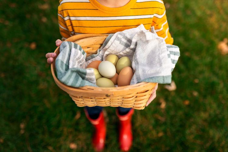 Man holding ice cream in basket on field