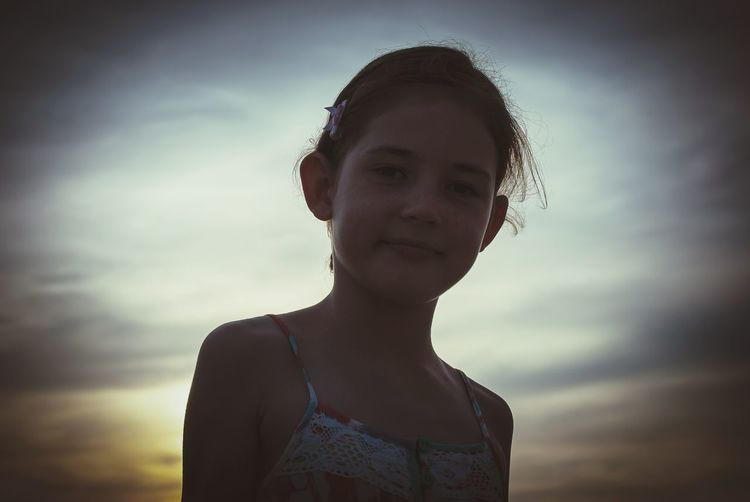 Low angle portrait of girl against cloudy sky during sunset