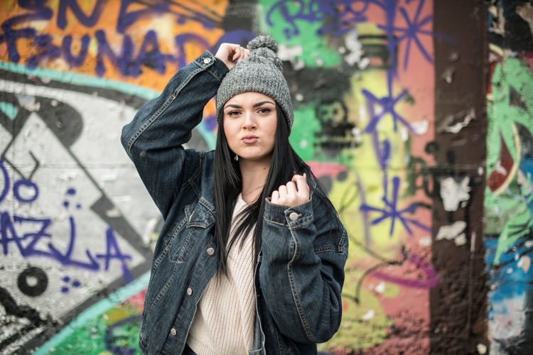 Young woman standing against graffiti wall