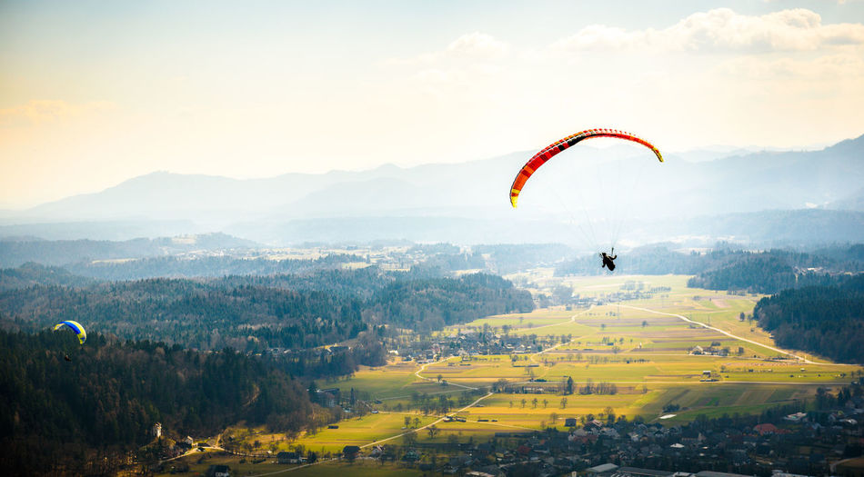 Person paragliding over landscape against sky