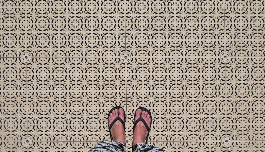 Low section of woman standing on patterned floor