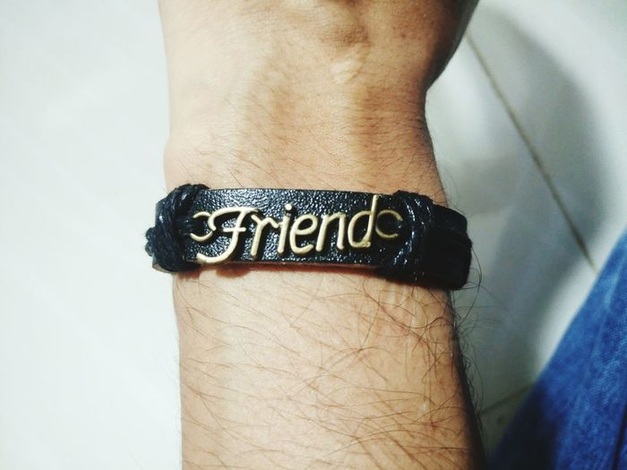 Cropped Image Of Hand Wearing Bracelet With Friend Text