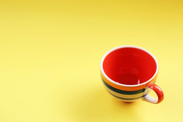 Coffee cup on table against yellow background