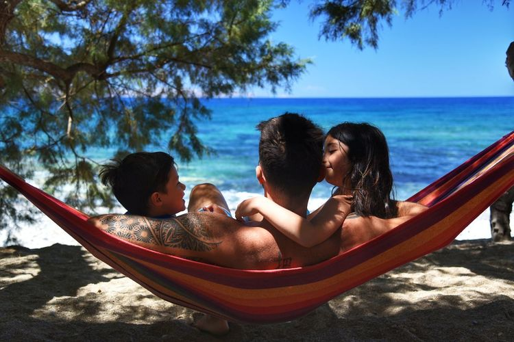 Rear View Of Father With Children Relaxing In Hammock At Beach