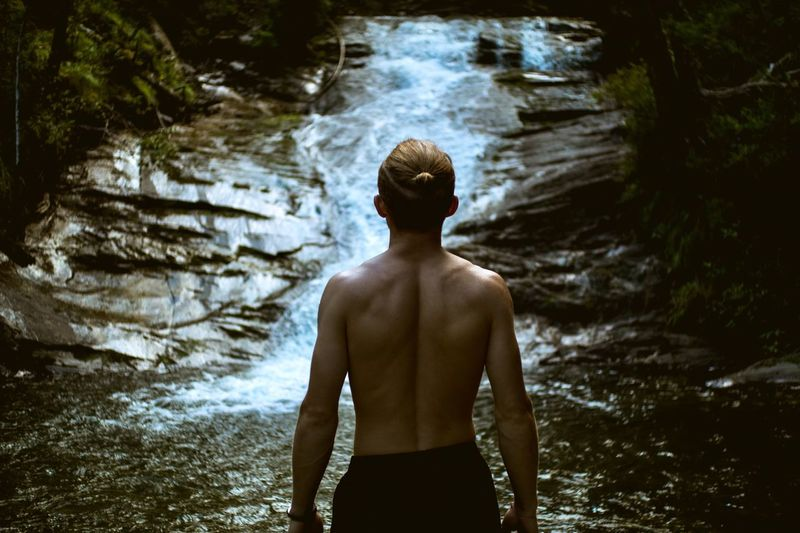 Rear View Of Shirtless Man Standing Against Waterfall