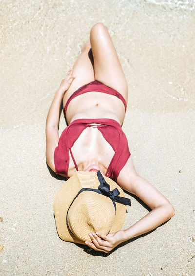 High angle view of woman relaxing on sand at beach