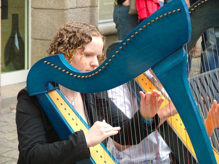 Musician playing harp on street