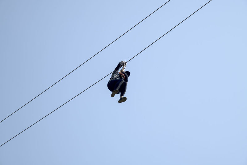 Low Angle View Of Woman Zip Lining Against Clear Sky