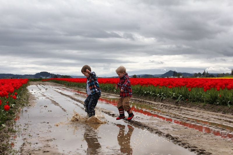 Boys Jumping On Puddle At Road Amidst Field Against Cloudy Sky