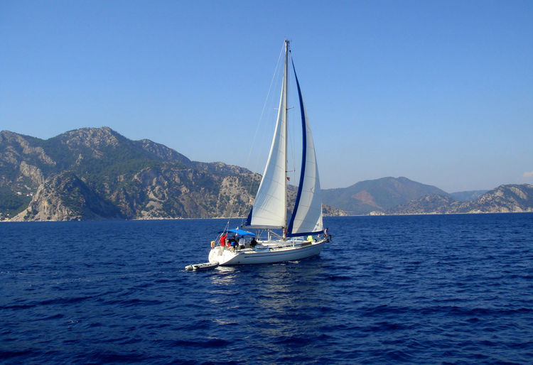 Yacht with white sail sailing on a calm sea on a background of mountains. Beauty In Nature Blue Blue Wave Boat Clear Sky Copy Space Mode Of Transport Mountain Mountain Range Nature Nautical Vessel Rippled Sailboat Sailing Scenics Sea Tranquil Scene Tranquility Water Waterfront Telling Stories Differently