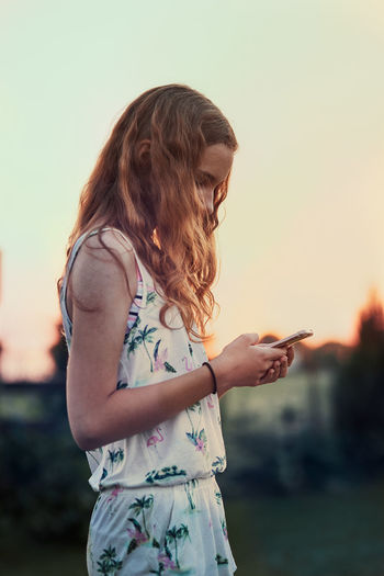 Side view of girl using mobile phone against sky during sunset