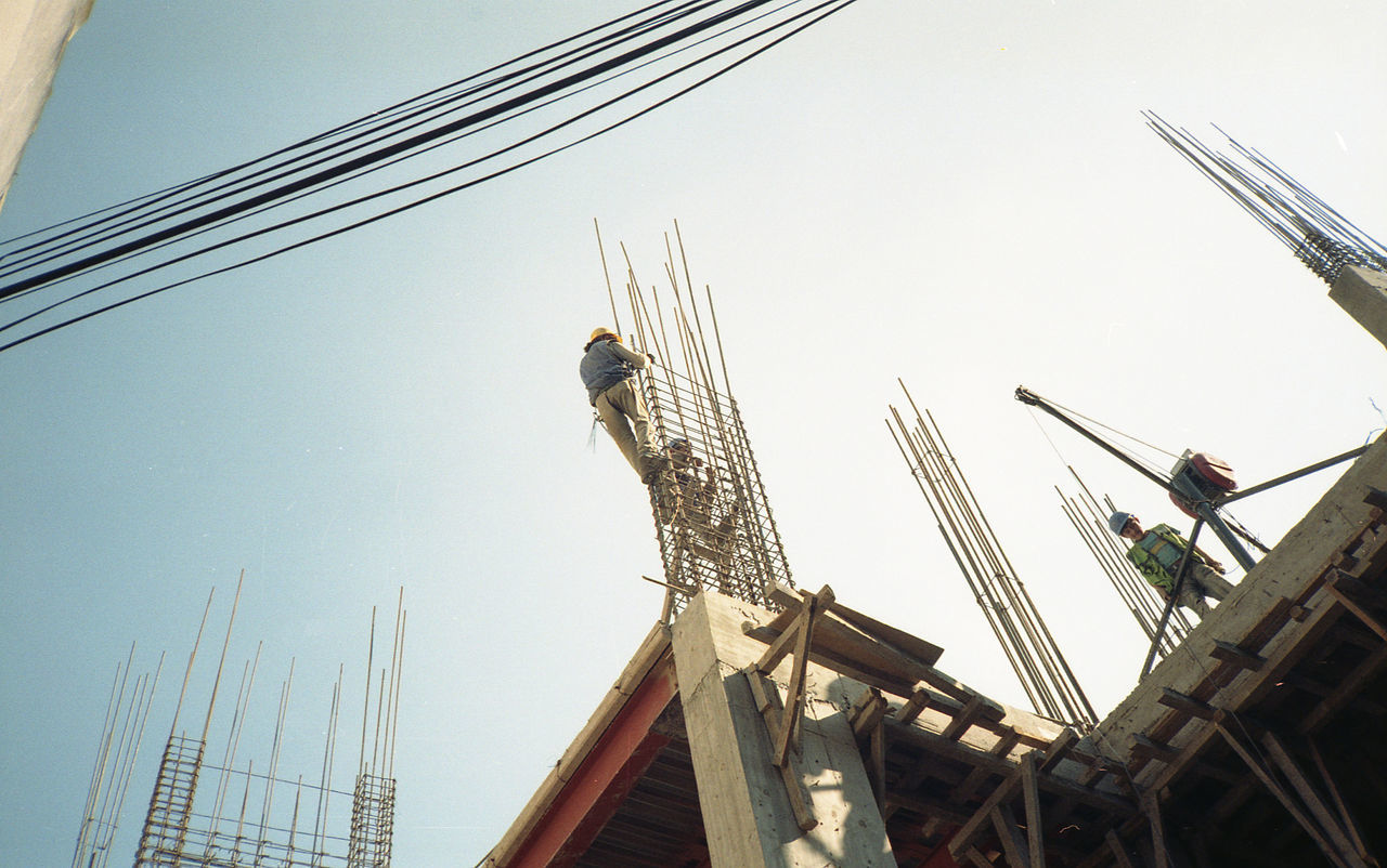 Low angle view of construction workers making reinforcing bar against clear sky