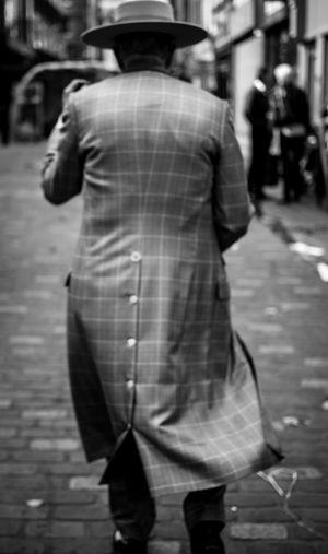 Rear view of man and woman walking on sidewalk