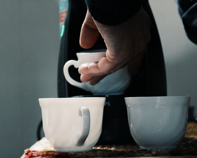 Cropped Image Of Man Hand Putting Cup In Coffee Maker