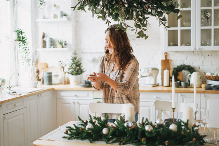 Attractive curly hair woman in plaid shirt takes photo gift box on festive table with fir