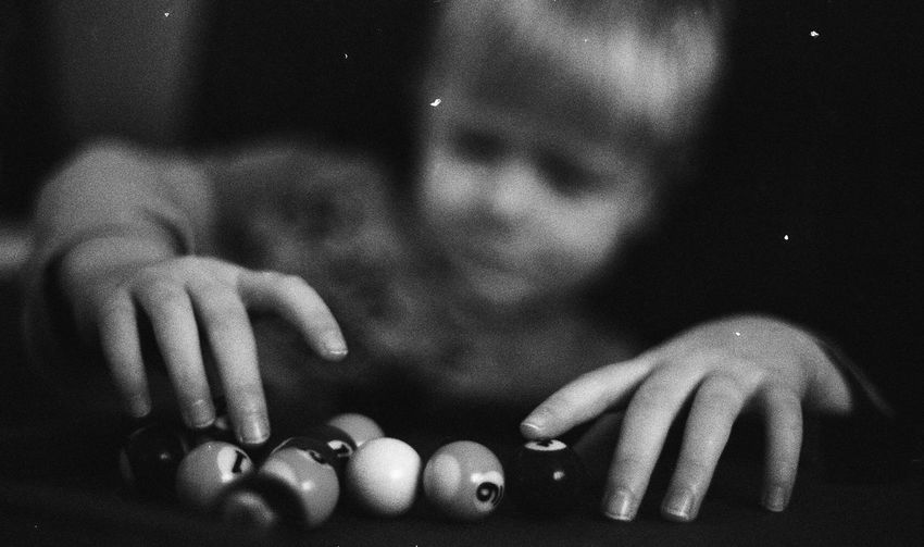 Close-up of boy holding small pool balls