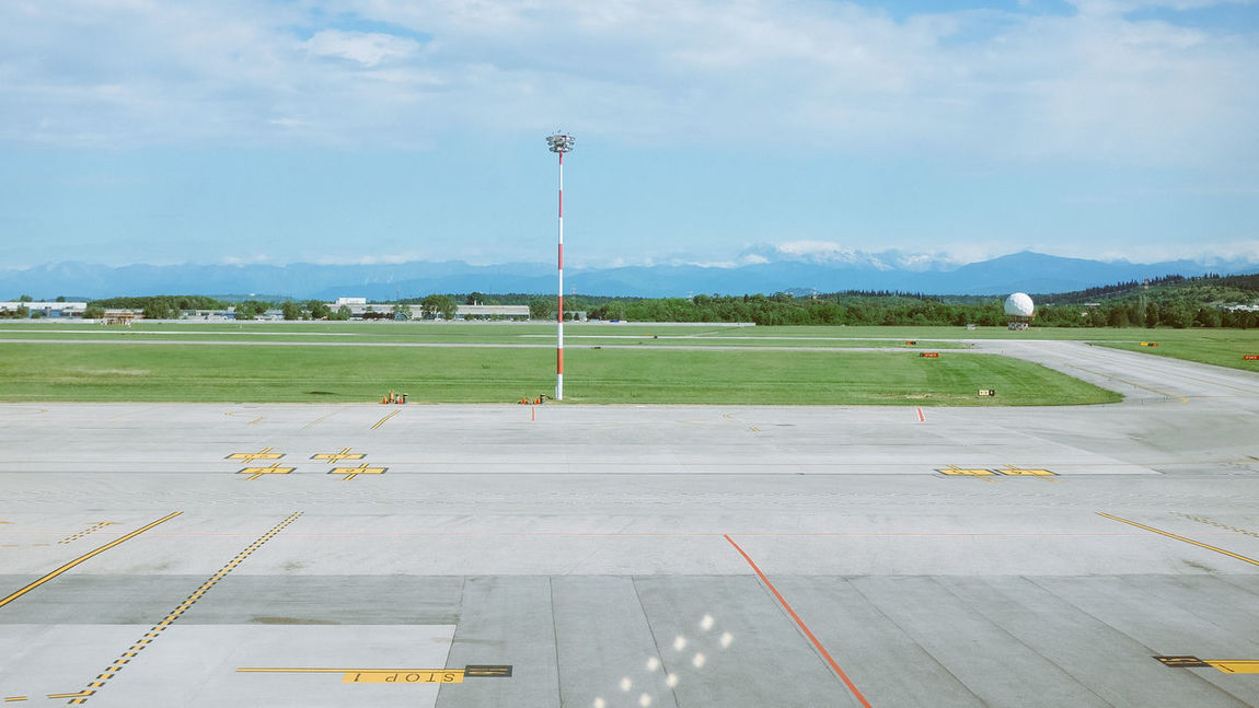 Airport runway with mountains in the background Airplane Airport Airport Runway Day Grass Green Color No People Outdoors Passenger Boarding Bridge Runway Runway Sky Transportation