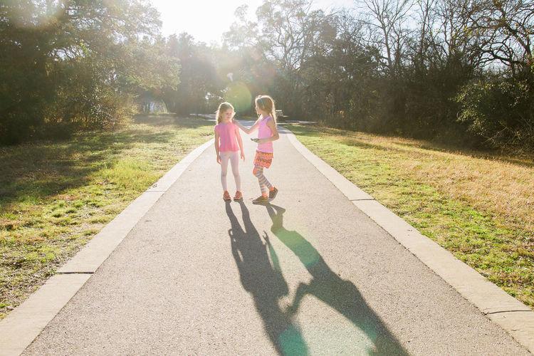 Full length of siblings standing on footpath in park against trees