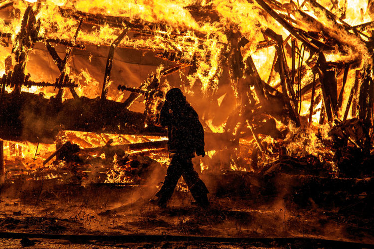 Firefighter walking by burning fire at night