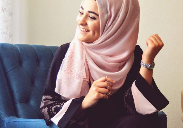 Smiling young woman wearing hijab sitting on sofa at home