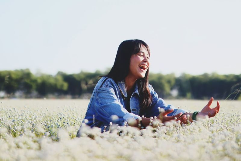 Happy Teenage Girl Amidst Flowering Plants On Field Against Clear Sky