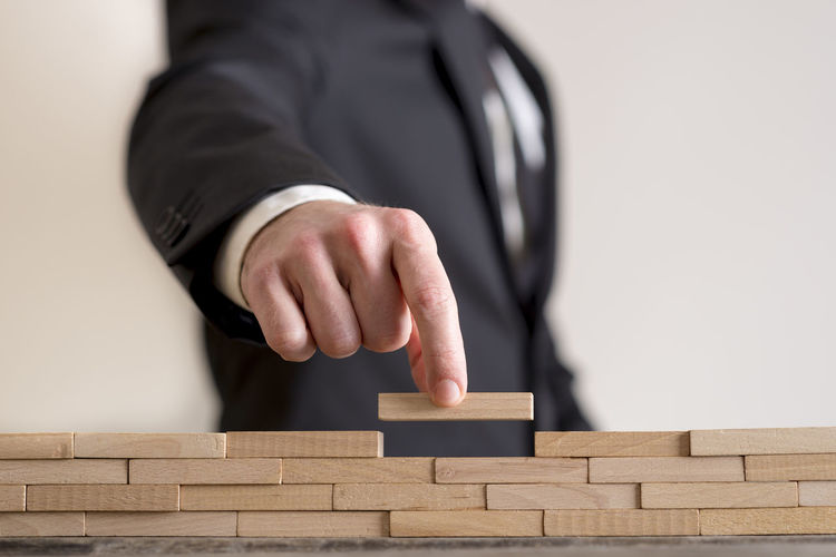 Midsection of businessman arranging wooden blocks