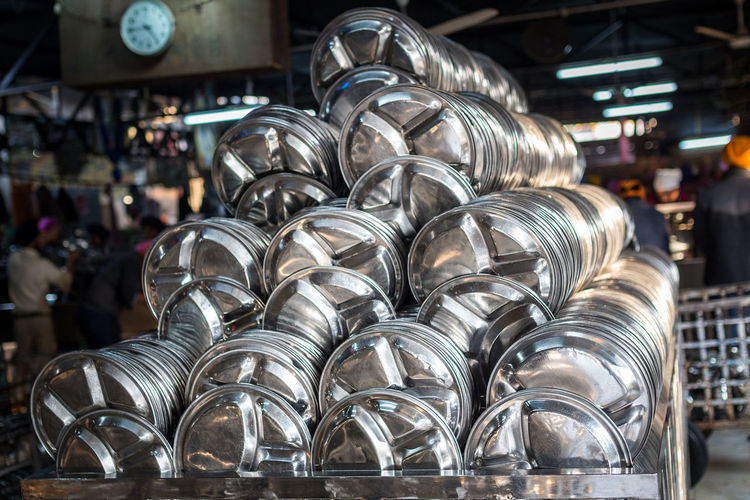 Steel plates arranged in large container at restaurant