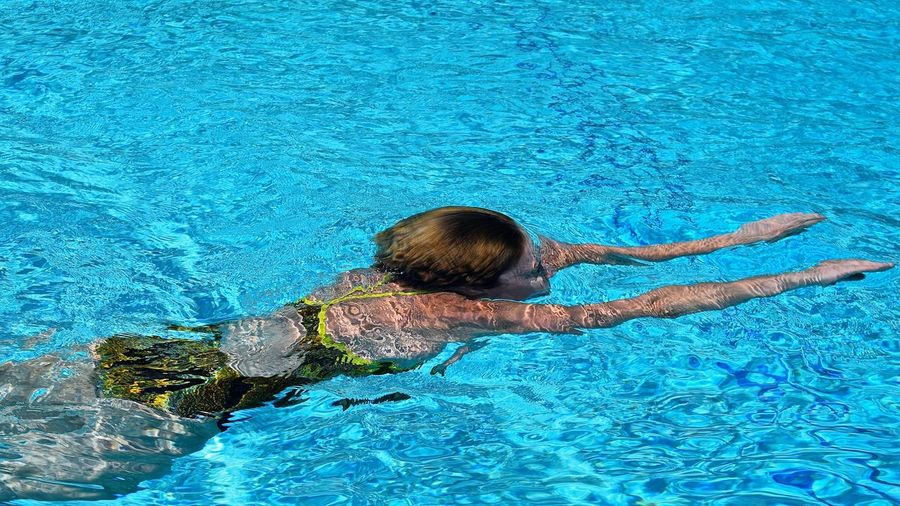 High Angle View Of Woman Swimming In Pool On Sunny Day