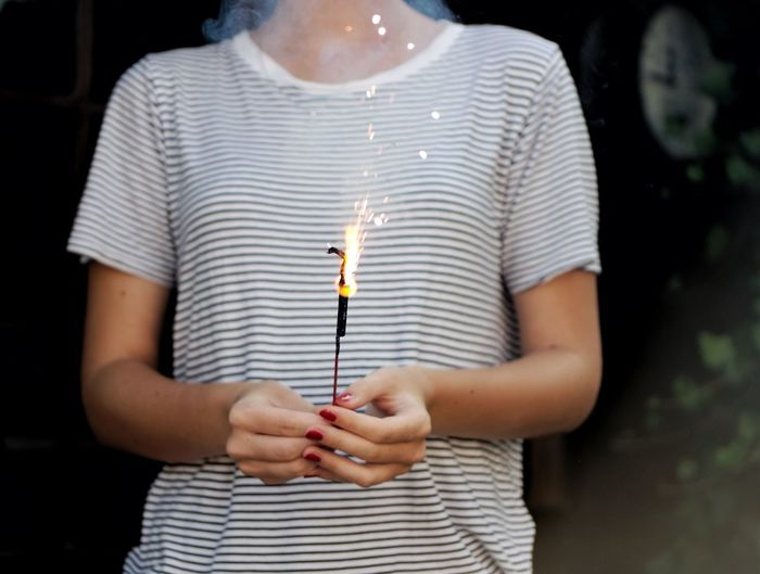 Midsection of woman holding lit sparkler