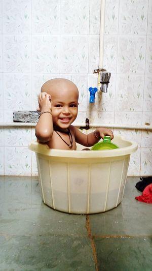 Portrait Of Smiling Girl Sitting In Bathtub