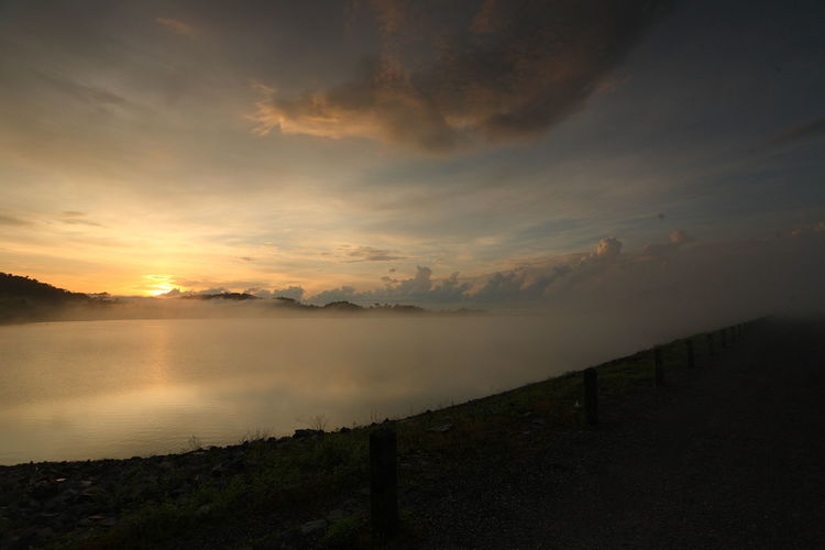 Beautiful landscape with fog and mountain at water dam in the during the sunrise of Thailand Sky Beauty In Nature Scenics - Nature Water Tranquil Scene Tranquility Cloud - Sky Sunset Lake Idyllic Non-urban Scene Reflection No People Nature Environment Landscape Remote Sun Outdoors Sunrise Fog