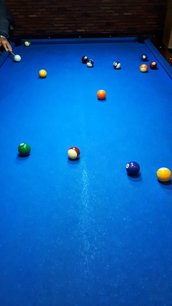HIGH ANGLE VIEW OF MULTI COLORED BALLS ON TABLE IN POOL