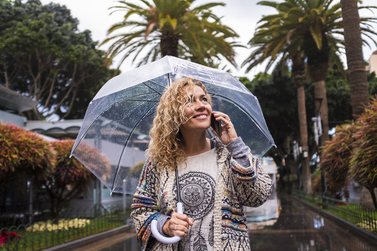 Woman with umbrella talking over phone while standing during rainy season