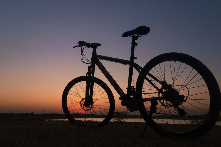 Silhouette bicycle against clear sky during sunset